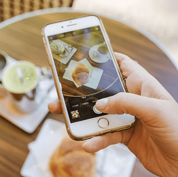 Healthified foods - to eat or not to eat? Picture of an iPhone taking a picture of a table of food.