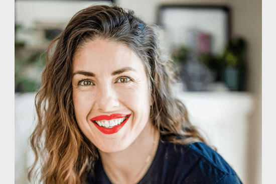 Paleo to Intuitive Eating: picture of a brown hair women's face. She is smiling and wearing bright red lipstick.