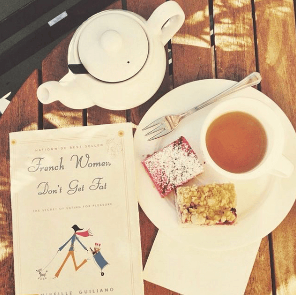 "5 Ways to Stop Food Guilt: Image with a white teapot, plate, and cup of tea. Two dessert bars and a silver fork. Book titled ""French Women Don't Get Fat""."